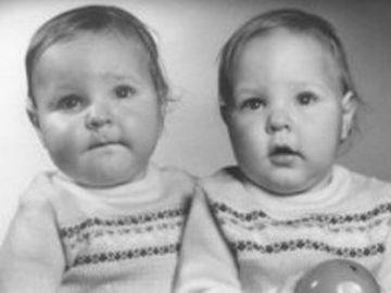 Sie sehen eineiige Zwillinge im Babyalter. Das Foto ist schwarz, weiß. Ein Kind hat einen Ball in der Hand.